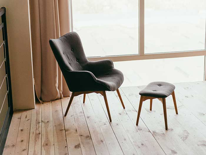 Single chair and foot rest on wooden floor